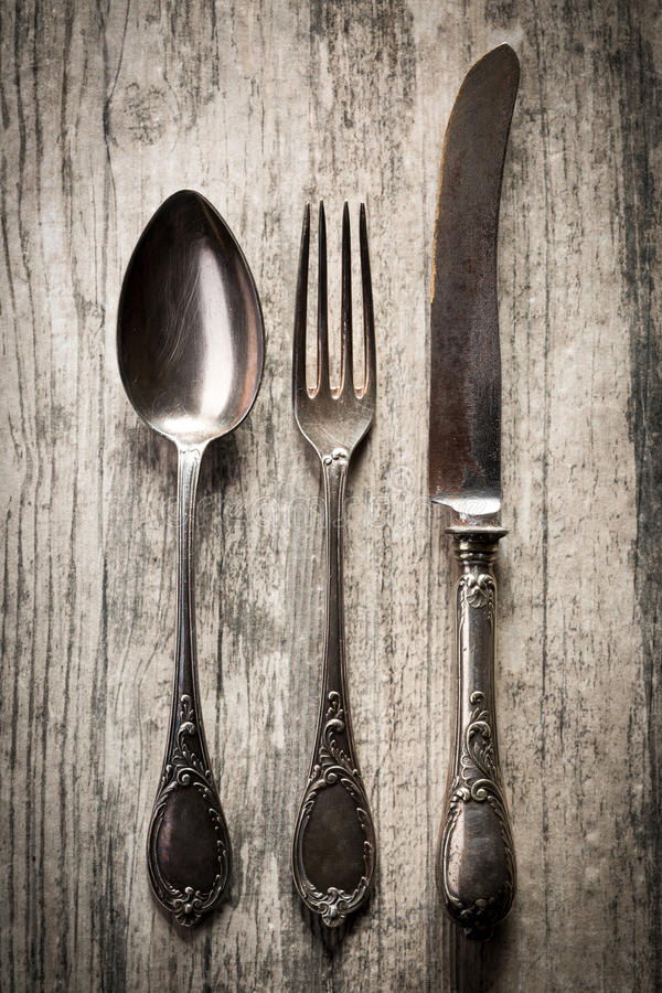 Old spoon, fork and knife on wooden background. Old antique spoon, fork and knife on dark wooden background royalty free stock image