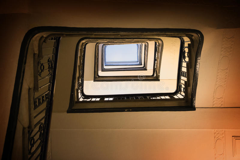 Old square spiral stairway case from below stock photography