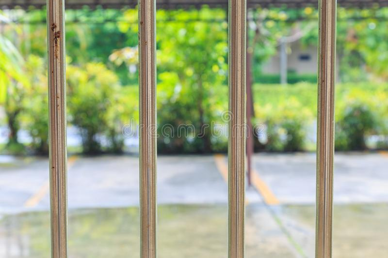 An old stainless rail fence and outside is parking and garden. royalty free stock photography