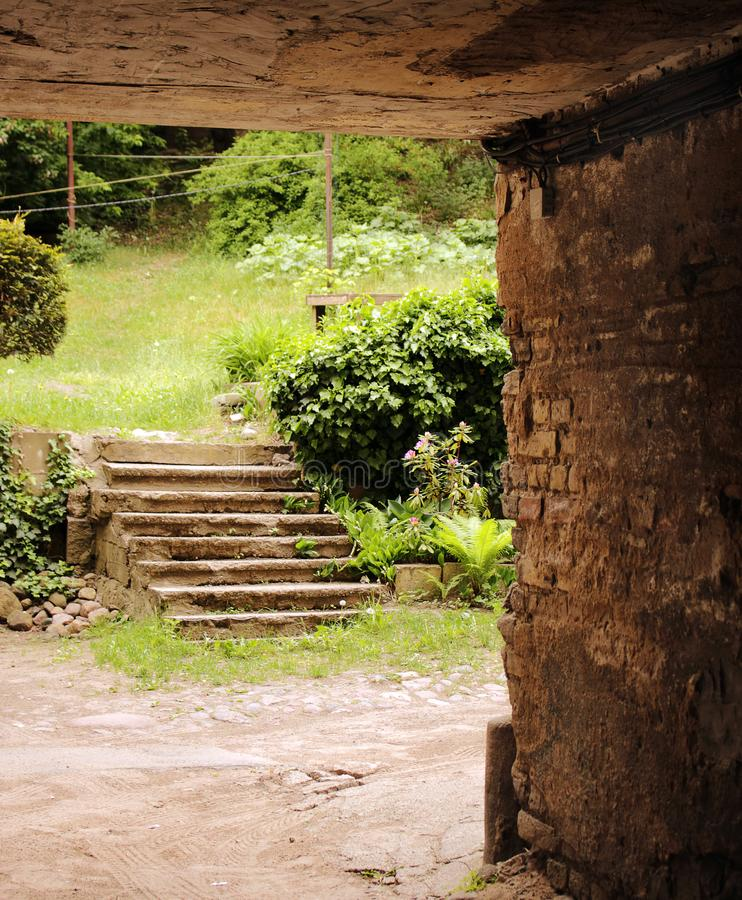 Old stairs in old town yard with greenery royalty free stock images