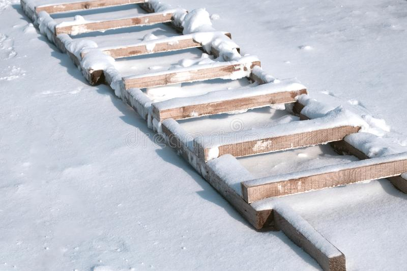 Old stairs in snow, homemade wooden. Ladder royalty free stock photography