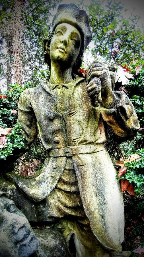 Old statue at Swan house Atlanta GA. This statue of a boy with a friend boasts the coming of manhood. It is weathered with dark stains of time stock photos