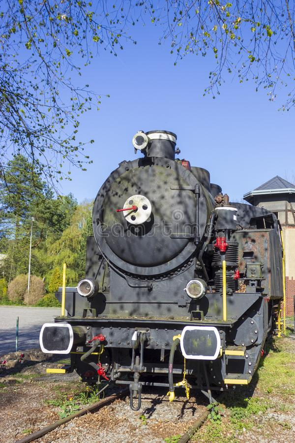 Old steam locomotive on rails. In foreground are trees blue sky stock photo