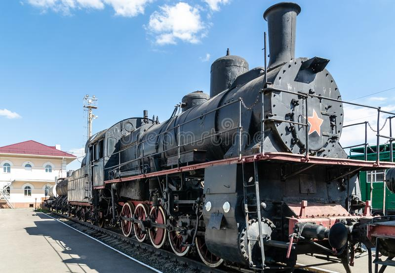 Old steam locomotive beside a railway station platform. Retro train royalty free stock image