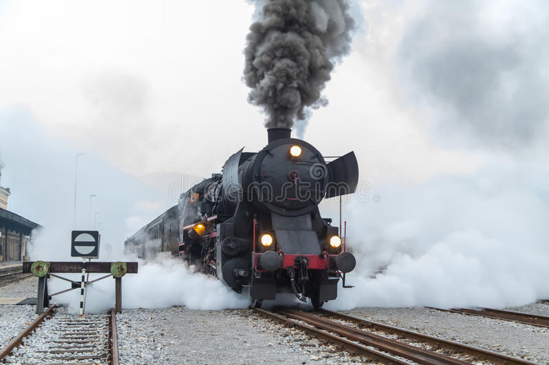 Old steam train leaving the railway station in Nova Gorica, Slovenia. Europe. Lots of black and gray steam hiding the locomotive, full frame, XXXL royalty free stock images