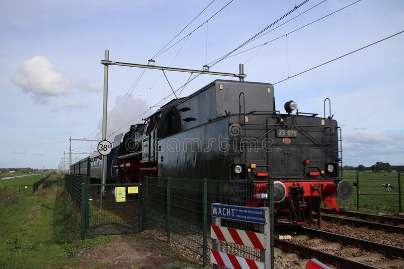 Old steam train from the SSN organization in Rotterdam running at the railroad track in Nieuwerkerk aan den IJssel in the Netherla royalty free stock photo