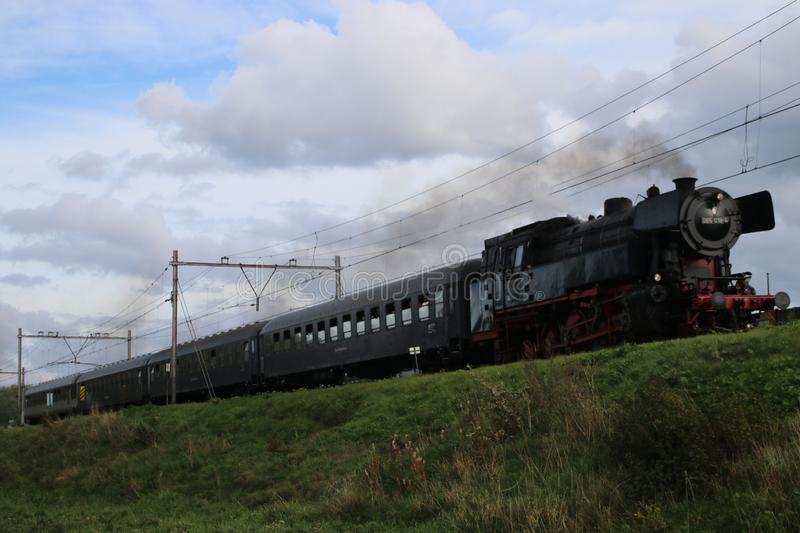 Old steam train from the SSN organization in Rotterdam running at the railroad track in Nieuwerkerk aan den IJssel stock image