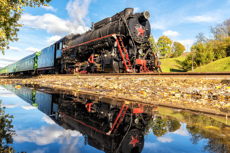 Old steam train at the station with reflection. Old steam train at the station on sunny day with reflection in the water, close-up royalty free stock photo