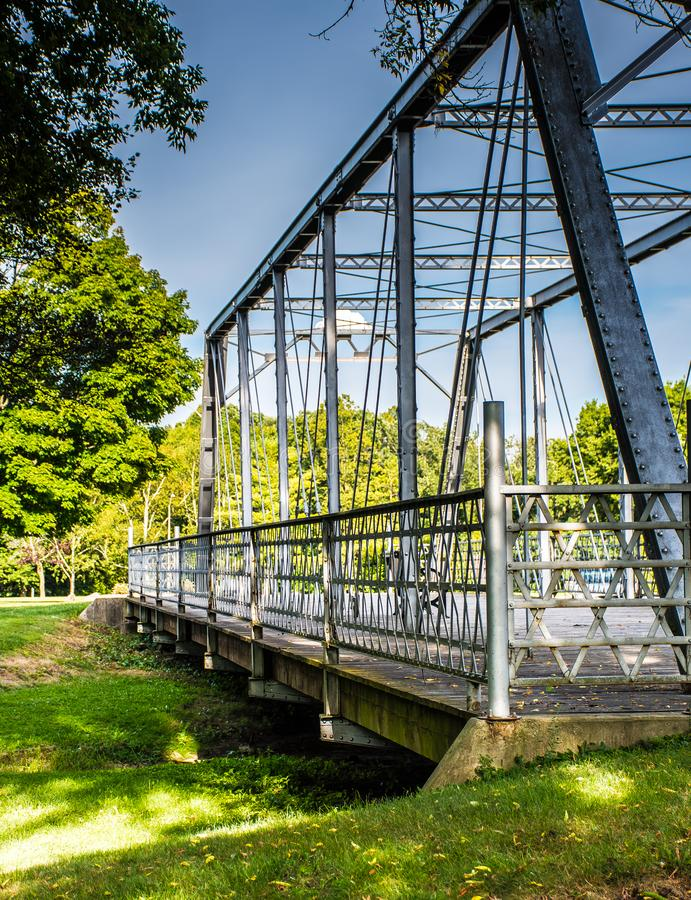 Old Steel Bridge Built in 1898 over Green Grass and under Blue Sky stock image