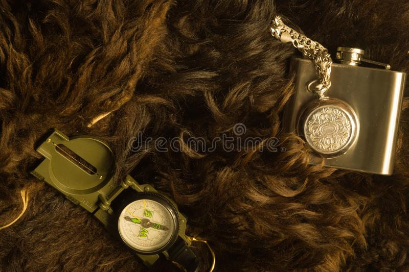 Old steel clock with the compass and the flask on the fur background. Modern compass and old clock on fur background. navigation stock image