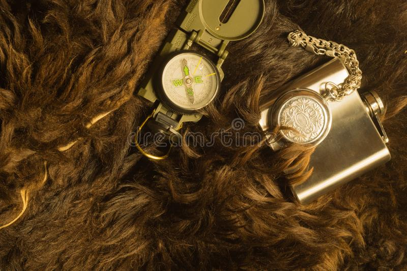 Old steel clock with the compass and the flask on the fur background. Modern compass and old clock on fur background. navigation royalty free stock image