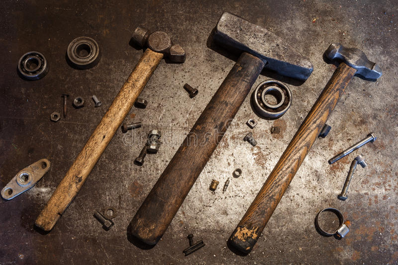 The old steel hammers with wooden handles and some bolts, nuts, bearings, valves, washers, nails on the metal background. Three old steel hammers with wooden stock image
