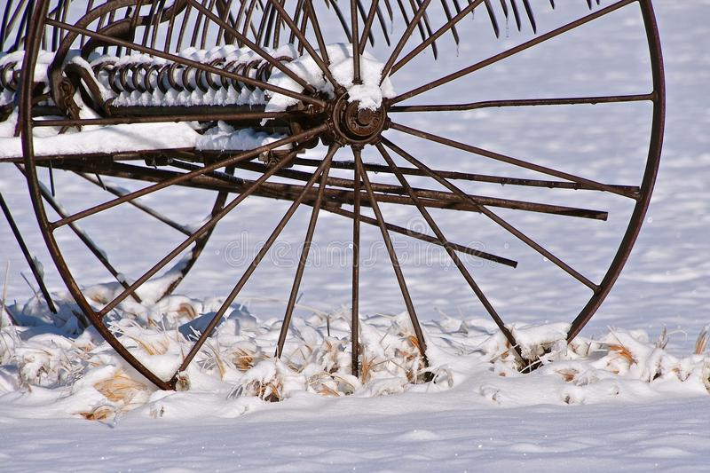 Old metal dump rake left in the snow. An old steel wheeled dump rake after a snowfall in a rancher farm setting setting stock photography