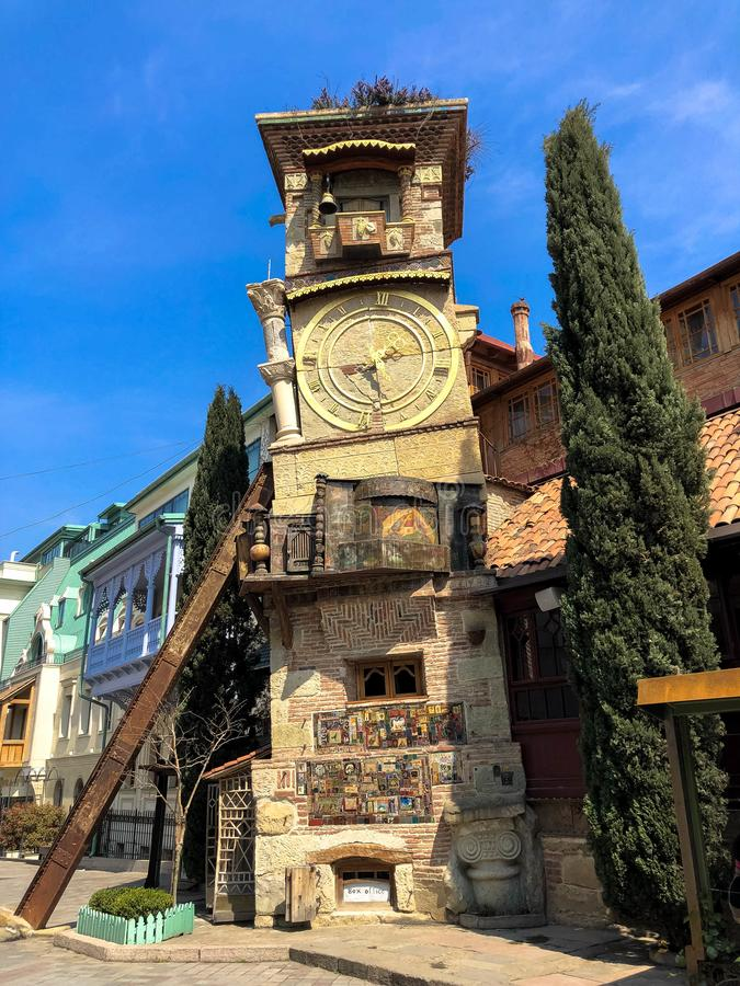 Old stone ancient carved beautiful antique European clock tower with dial on the background of the blue sky and the tourist city. European old architecture stock photos