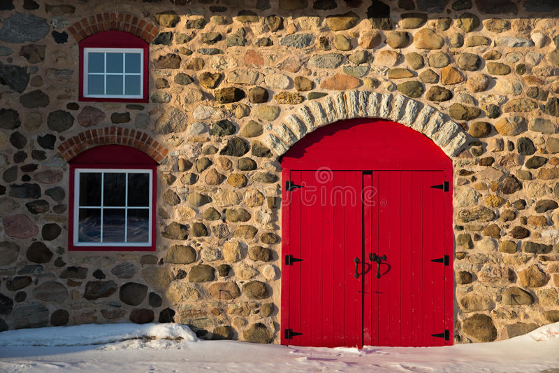 Red Doors Stone : Old stone barn with bright red door stock image