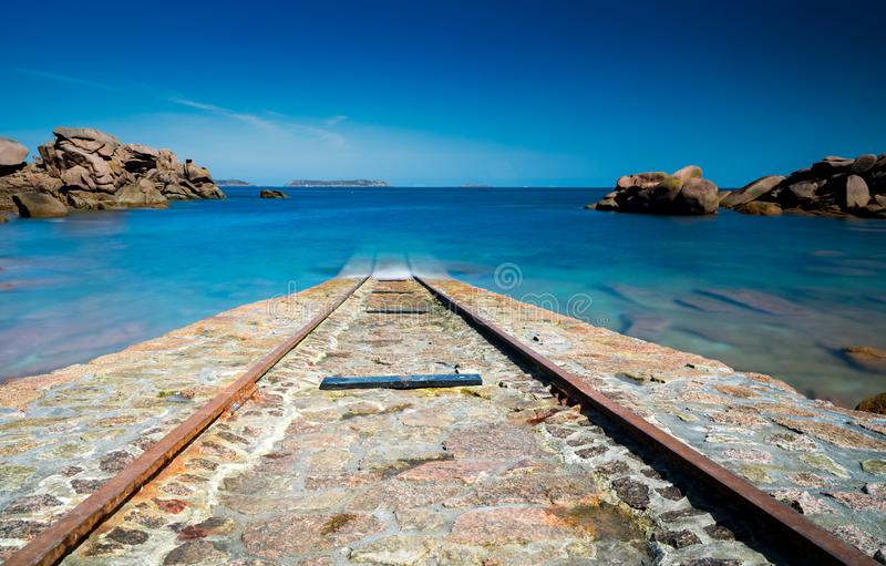 Old stone boat ramp for rescue ships leading into a calm blue ocean on the coast of Brittany stock images