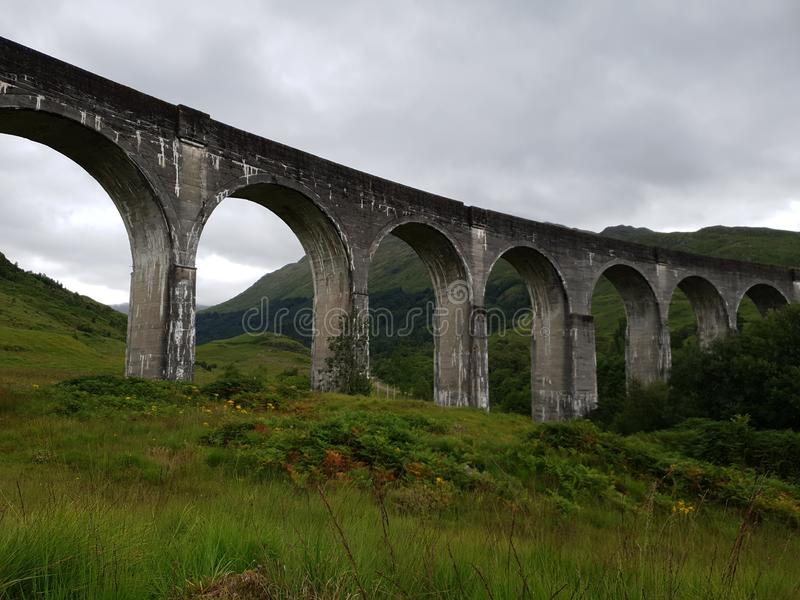 Old Stone bridge Harry Potter train Glenn. Mountain and Forest green landscapes stock image
