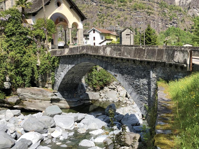 An old stone bridge over the Rovana River in the hamlet of Rovana The Rovana Valley or Valle Rovana, Val Rovana or Das Rovanatal. Canton of Ticino stock photography