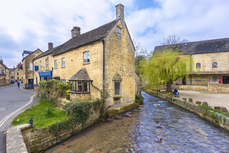 Old stone buildings stand along a river at Bourton On The Water, England stock images