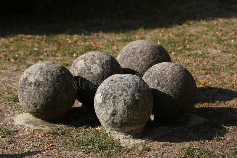 Old gray cannonballs lie on the ground royalty free stock photo