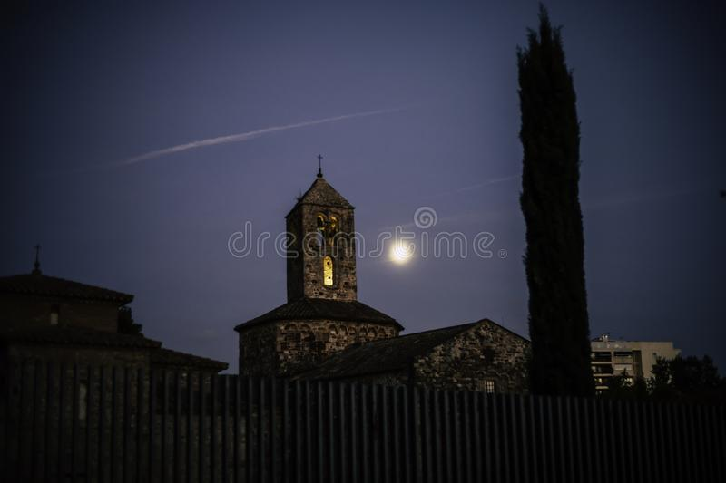 Old stone church on an evening with the moon close to the bell tower royalty free stock photos