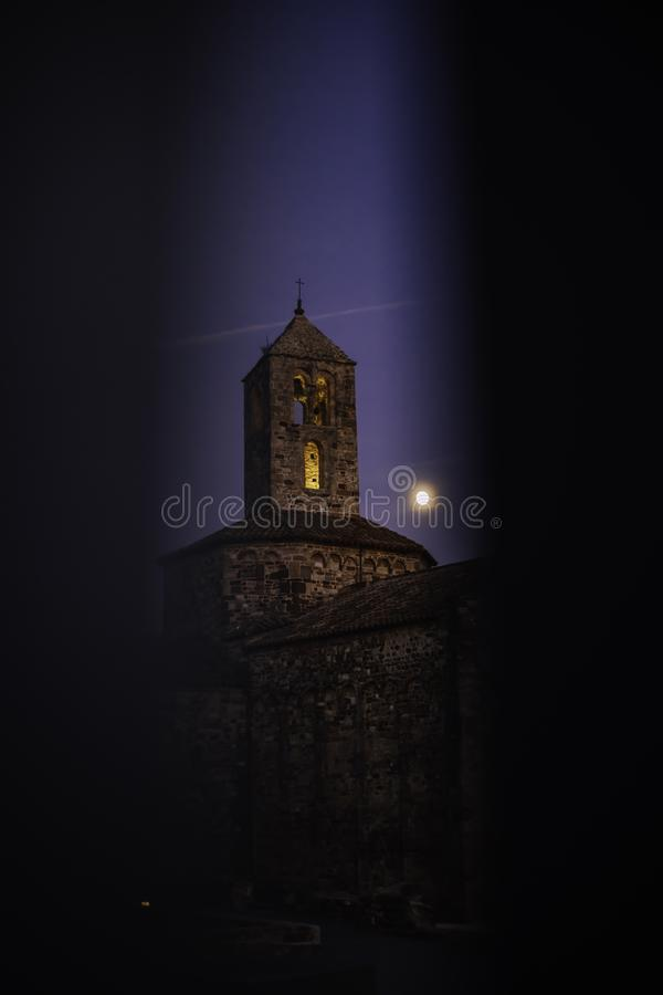 Old stone church on an evening with the moon close to the bell tower seen through gate stock photo