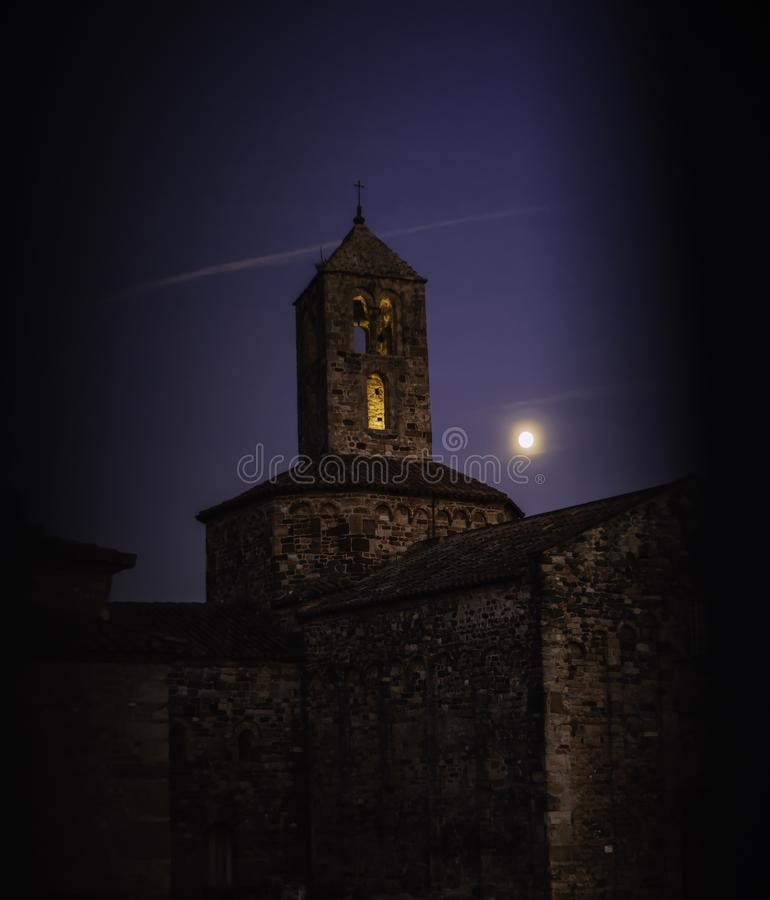 Old stone church on an evening with the moon close to the bell tower seen through gate stock photography
