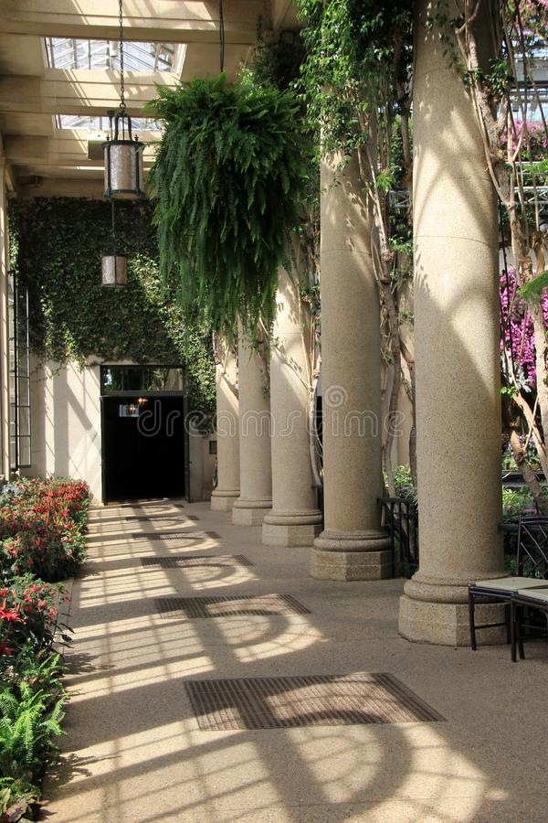 Old stone columns with plants and flowers draped around them, Longwood Gardens, PA, 2017. Gorgeous stone columns with exotic orchids and plants draped all around stock photos