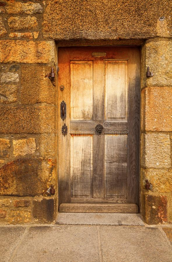 Old stone doorway with ancient weathered wooden door. Stone doorway on an ancient building on Mont Saint Michel France with old weathered wooden door royalty free stock photos