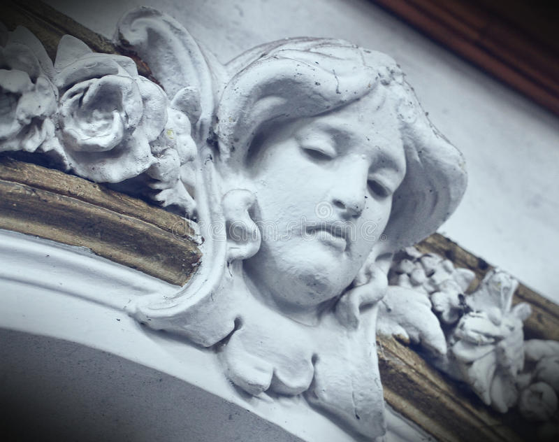 Old stone face. In an old house stock photo