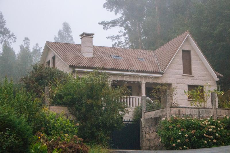 Old stone house with beautiful garden in morning fog. Rural cottage in village in forest. Cozy residence with trees and flowers. stock photos