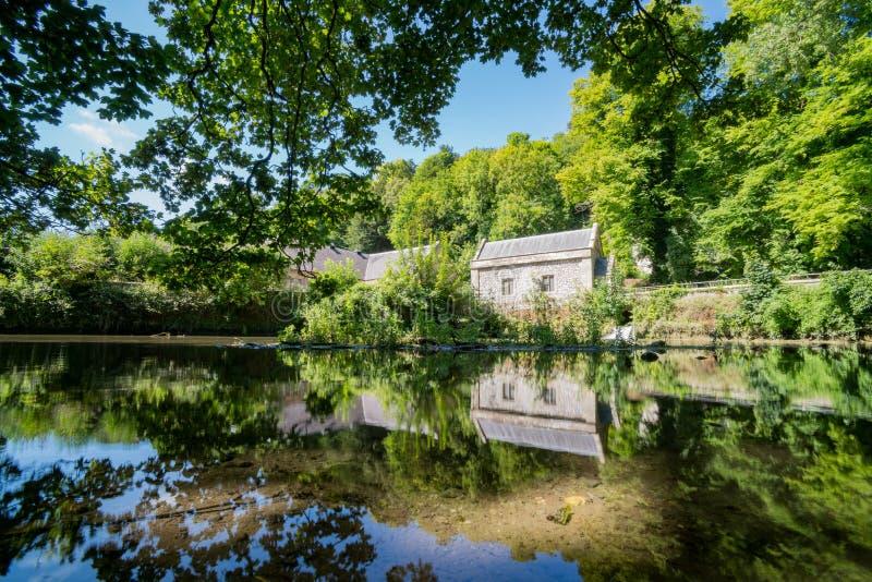 Old stone house with beautiful reflection. Around Swanbourne Lake, Arundle, United Kingdom royalty free stock photos
