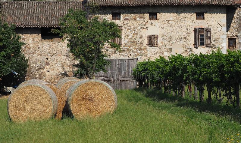 Old stone house with a large wooden gate at the center. On the left a row of hay bales and on the right a row of vi royalty free stock photography