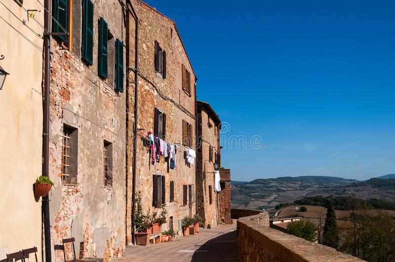 Old stone houses with colored clothing . Pienza, Italy. stock images