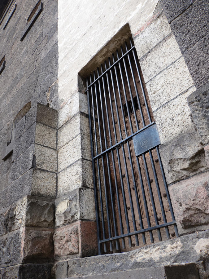 Old stone jail wooden door with iron bars. Old wooden door of stone jail with iron bars royalty free stock image