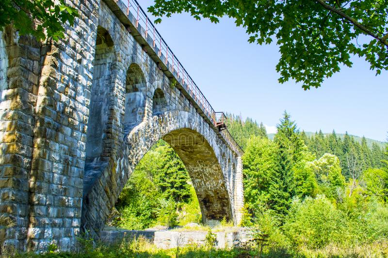 Old stone railway bridge. Of the times of the Austro-Hungarian Empire in Ukraine. The acting arch bridge built in 1895 over a mountain river Prut in tourist stock images