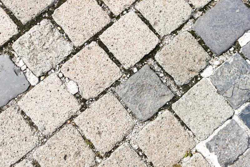 Old granite cobblestone pavement or road pattern texture. Regular rows of granite paving stones background stock image