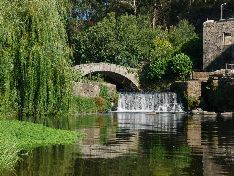 Old stone ruins and ancient Roman bridge on River Este in Touginho, Portugal. Beautiful bright sunny day in summer royalty free stock photo