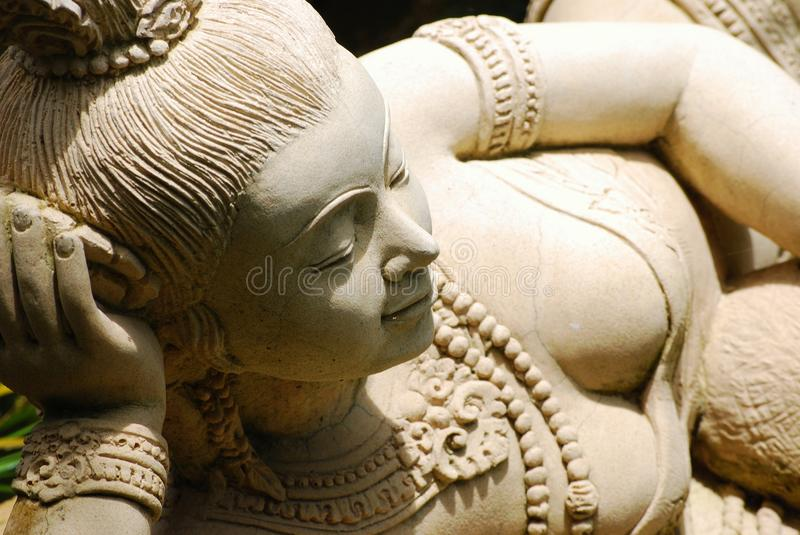 Old stone statue. Of an asian lady stock photography