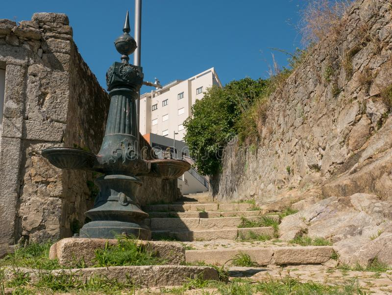 Old stone steps and vintage drinking fountain in Porto, Portugal. Bright sunny day in summer. Old stone steps and vintage drinking water fountain in Porto stock images