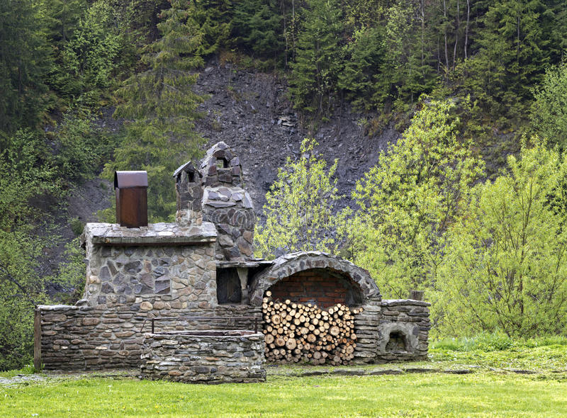 Old stone stove with wood and smokehouse in the mountains royalty free stock photos