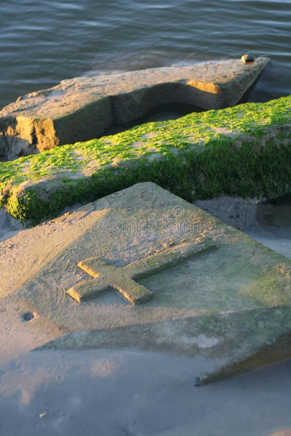 Old stone tombstones covered with green algae. On the beach in normandy royalty free stock photography