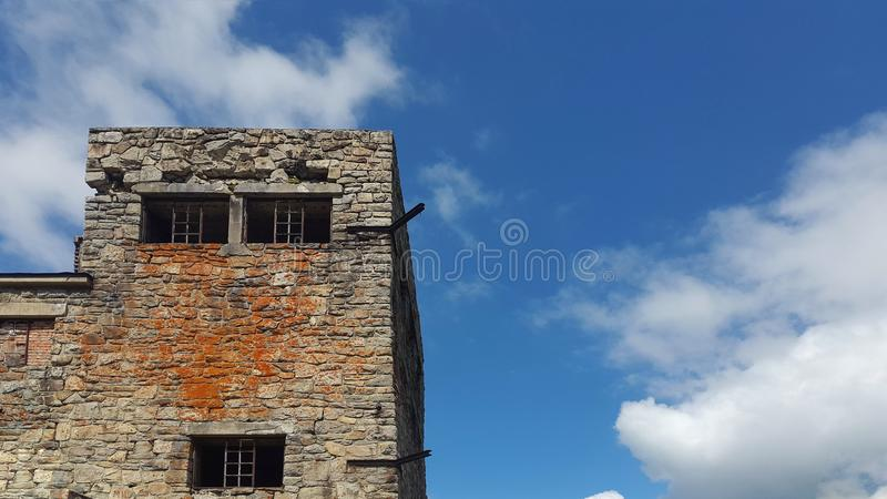The old stone tower with Windows on sky background with clouds stock photography