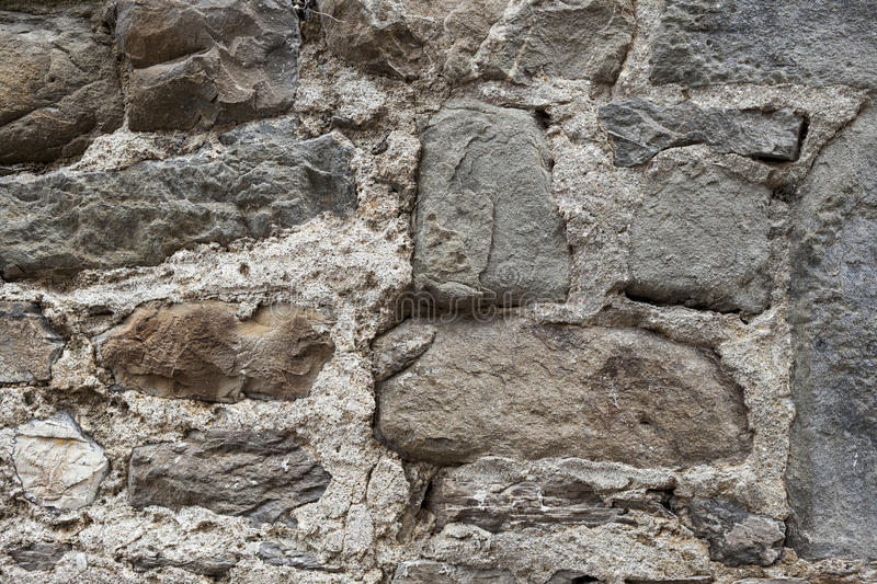 An old stone wall brown large stones. Classical masonry walls of medieval castles in Europe. royalty free stock photos