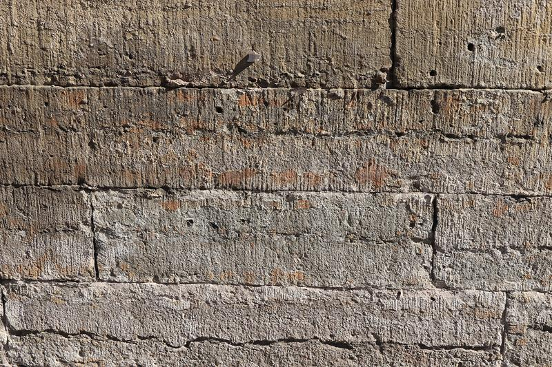 Old stone wall with cracks, natural concrete background, old natural texture of an ancient stone. It is used for decoration of. Buildings and embankments, a royalty free stock image