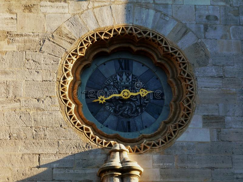 Old stone wall with elegantly designed clock. With stone lace decoration, golden handles and elegant face platenwith roman numerals stock photos