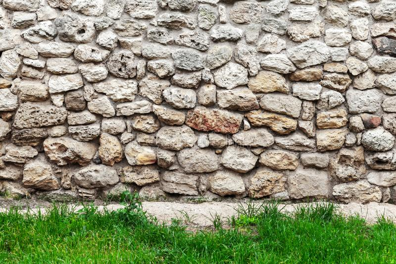 Old stone wall and fresh green grass. Front view, background photo texture stock image