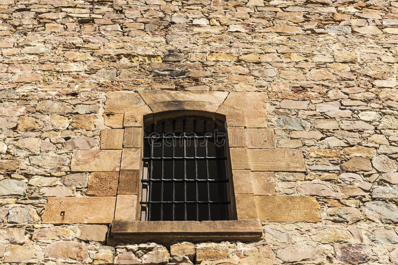 Old stone wall with a latticed window stock photography