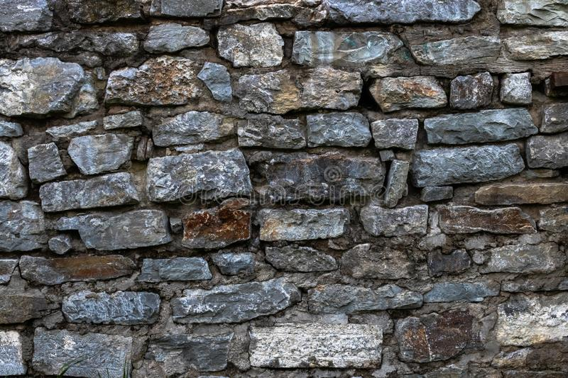 The old stone wall is lined with stone of various shades of gray and brown. Background stock images