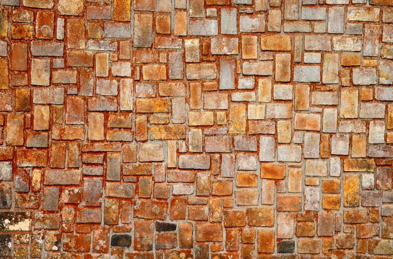 Old stone wall in orange and grey colors. Brickwork closeup photo for background. Rustic brick masonry. royalty free stock photo
